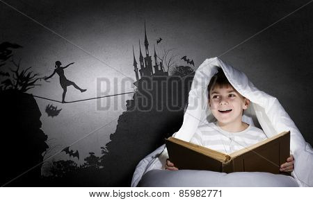 Little cute boy reading book in bed under blanket