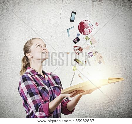 Young woman in casual holding opened book with icons flying out
