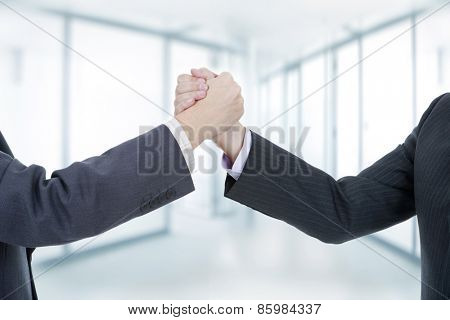 two businessmen in a handshake, at the office