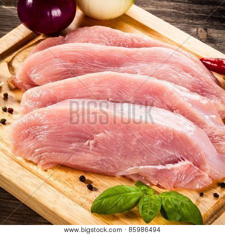 Raw chicken breasts on cutting board