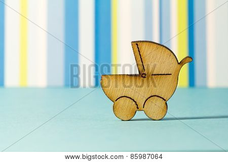 Wooden Icon Of Baby Carriage On Blue Striped Background
