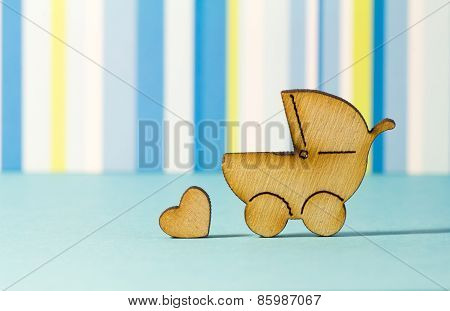 Wooden Icon Of Baby Carriage And Little Heart On Blue Striped Background