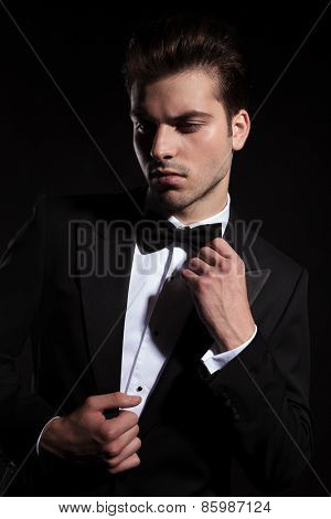 Young business man looking down while fixing his jacket and bowtie.