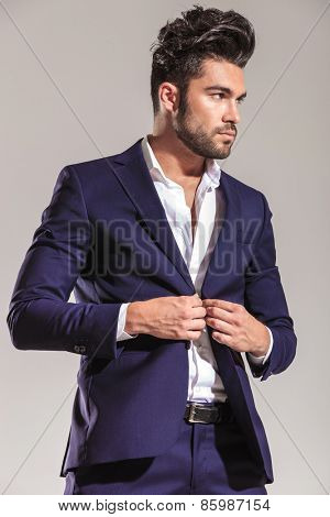 Handsome young business man looking away from the camera while closing his jacket.