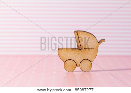 Wooden Icon Of Baby Carriage On Pink Striped Background