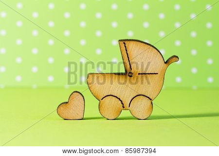 Wooden Icon Of Baby Carriage And Little Heart On Green Background