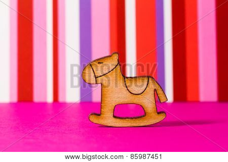 Wooden Icon Of Children's Rocking Horse On Red Striped Background