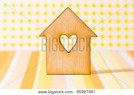 Wooden House With Hole In The Form Of Heart On Yellow Background