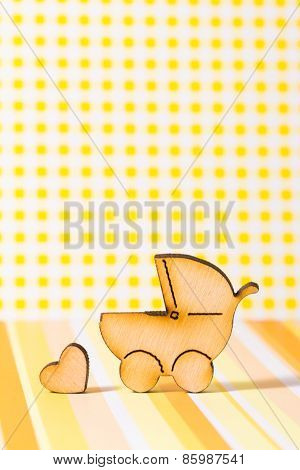 Wooden Icon Of Baby Carriage And Little Heart On Yellow Background