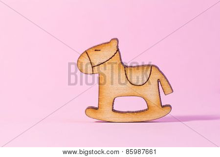 Wooden Icon Of Children's Rocking Horse On Pink Background