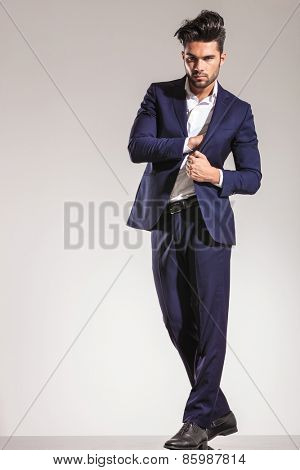 Young business man standing on grey studio background pulling his coat and putting something inside.
