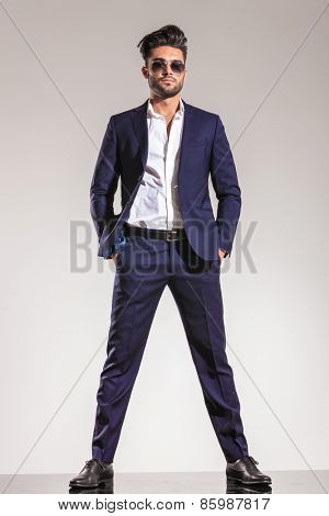 Full length image of a elegant business man looking at the camera while holding both hands in his pockets.