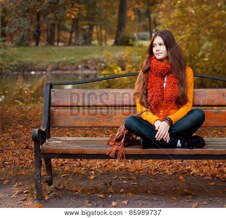 Girl on bench in autumn park