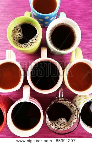 Many cups of coffee on pink table, top view