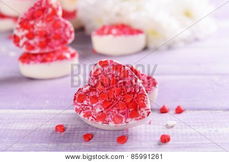 Delicious chocolate candies in heart shape on table close-up
