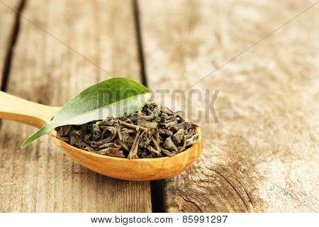 Green tea with leaf in spoon on old wooden table