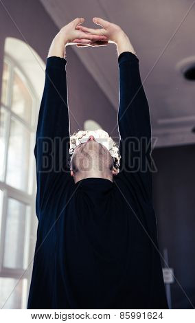 Young man stretching hands and looking up at gym