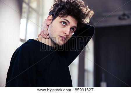 Young man stretching neck and looking up at gym