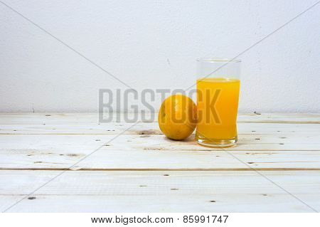 Glass Of Delicious Orange Juice And Oranges On Wooden Table Background