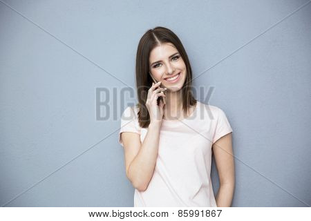 Happy young woman talking on the phone over gray background