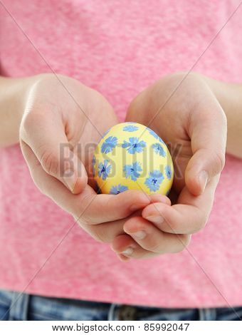 Girl holding painted egg in her hands, close-up