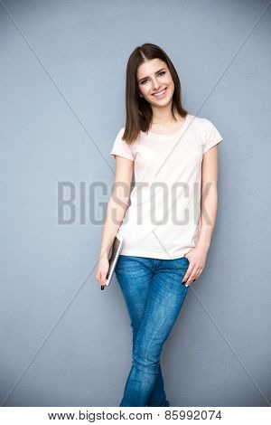 Cheerful young woman holding tablet computer over gray background