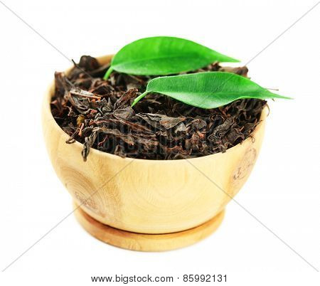 Wooden bowl with black tea with leaf isolated on white