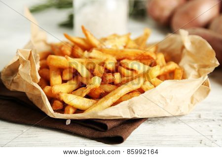 Tasty french fries on paper napkin, on wooden table background