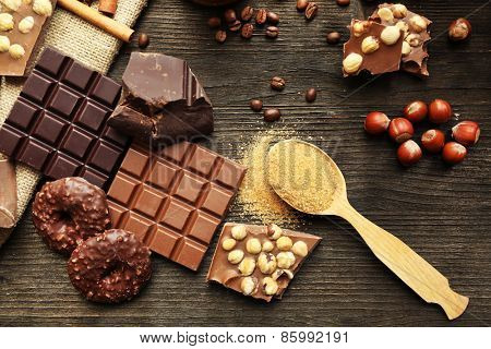 Still life with set of chocolate with nuts on wooden table, top view