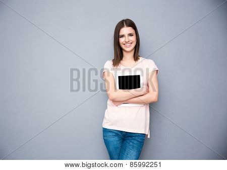 Young smiling woman holding tablet computer over gray background