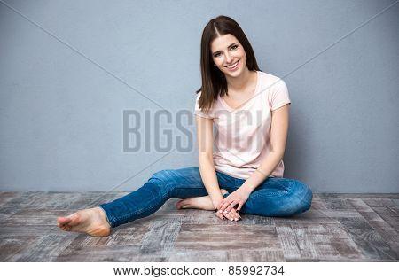 Smiling young cute woman sitting on the floor