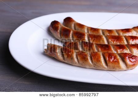 Grilled sausages on plate on table close up