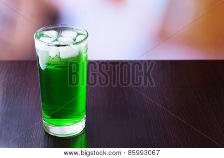Green cocktail on table on light background