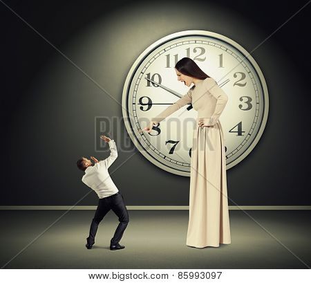 angry yelling woman pointing at scared man with in dark room with big clock on the wall