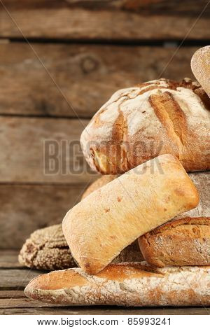 Different fresh bread on old wooden table