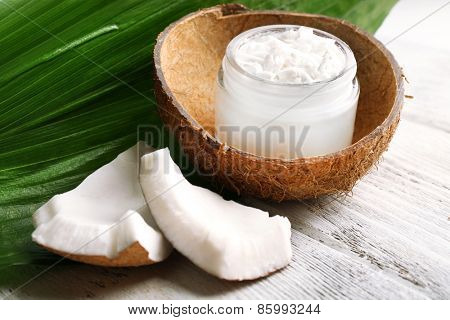 Fresh coconut oil in glass bottle and green leaf on wooden table background