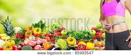 Healthy vegan diet. Woman measuring her body.