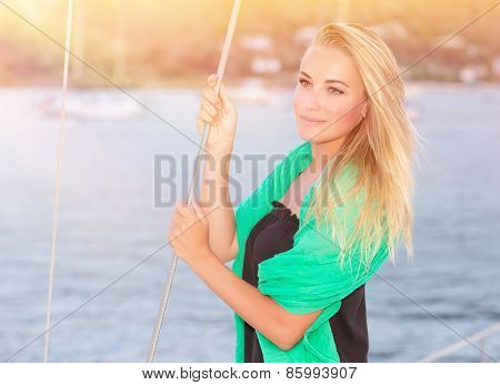 Portrait of pretty dreamy blond girl standing on the deck of luxury sailboat and enjoying beautiful view on sunset, happy summer vacation