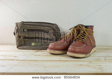 Still Life With Boots And Bag On Wooden Table Background.