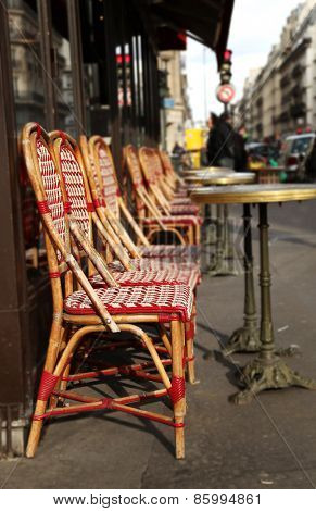 Red chairs and round table on the street in Paris, France.