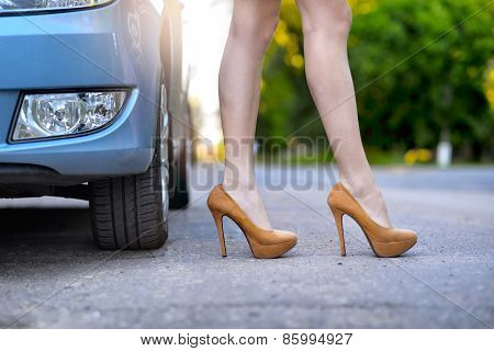 Sexy woman with long legs standing near the car on the road