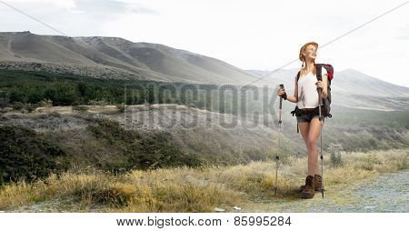 Young pretty girl tourist with backpack on back hiking at summer
