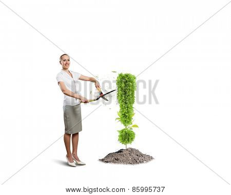 Young attractive businesswoman cutting plant in shape of exclamation mark