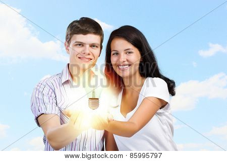 Young happy couple holding electric bulb in palms
