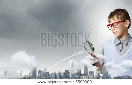 Cute school boy examining objects with magnifying glass