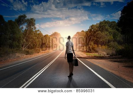 Back view of businesswoman standing on road and looking far away