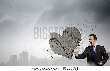 Young businessman breaking stone heart with punch