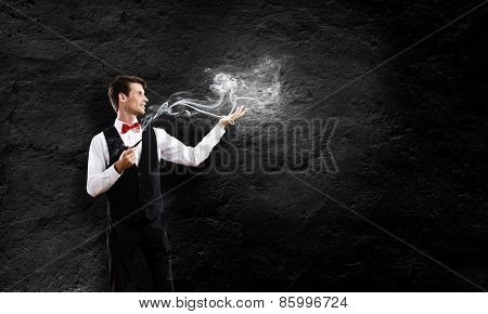 Young handsome businessman smoking pipe against black background