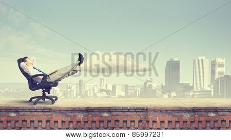 Confident businessman sitting on chair with legs up