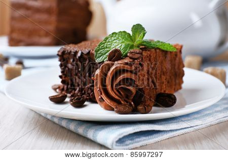 Tasty pieces of chocolate cake with mint and cinnamon on wooden table and blurred planks background